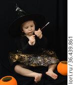 Милая двухлетняя девочка в костюме ведьмы сидит на черном фоне и разглядывает волшебную палочку. Стоковое фото, фотограф Наталья Гармашева / Фотобанк Лори