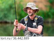 Portrait of mid adult fisherman on river, relaxing and fishing trouts. Стоковое фото, фотограф Zoonar.com/DAVID HERRAEZ CALZADA / easy Fotostock / Фотобанк Лори