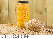 Glass bowl of raw chickpeas on wooden surface. Healthy and nutritious food. Стоковое фото, фотограф Яков Филимонов / Фотобанк Лори
