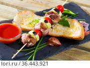 Baked shashlik of lamb with onion and tomatoes served with ketchup and bread. Стоковое фото, фотограф Яков Филимонов / Фотобанк Лори