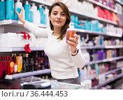 Happy girl choosing hair care treatments in cosmetics store. Стоковое фото, фотограф Татьяна Яцевич / Фотобанк Лори