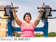 Young woman shakes her triceps using street chest press weight machine. Стоковое фото, фотограф Евгений Харитонов / Фотобанк Лори