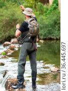 Fisherman fishing on the River, holding Fishing Rod. Стоковое фото, фотограф Zoonar.com/DAVID HERRAEZ CALZADA / easy Fotostock / Фотобанк Лори