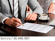 Businessman in gray suit sitting at office desk signing a contract... Стоковое фото, фотограф Zoonar.com/Ivan Mikhaylov / easy Fotostock / Фотобанк Лори