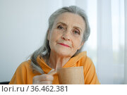Close-up portrait of pensive and calm mature woman with gray hair and holding a coffee mug. Стоковое фото, фотограф Ольга Балынская / Фотобанк Лори