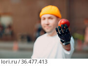 Young disabled man holds out to you apple with artificial prosthetic... Стоковое фото, фотограф Zoonar.com/Max / easy Fotostock / Фотобанк Лори