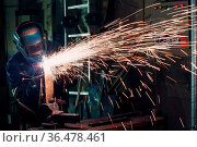 Man in mask cuts metal with plasma cutter. Helmet and spakrs. Стоковое фото, фотограф Zoonar.com/Max / easy Fotostock / Фотобанк Лори
