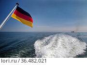 Blick von einem fahrenden Schiff auf eine Deutschlandflagge und die... Стоковое фото, фотограф Zoonar.com/Stefan Ziese / age Fotostock / Фотобанк Лори