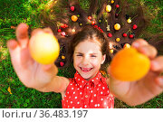 Fresh fruits, healthy food concept - girl lay with fruits on her hair. Стоковое фото, фотограф Zoonar.com/Oksana Shufrych / easy Fotostock / Фотобанк Лори