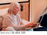 Senior Woman with laptop relaxing at glamping camping tent. Modern... Стоковое фото, фотограф Zoonar.com/Max / easy Fotostock / Фотобанк Лори