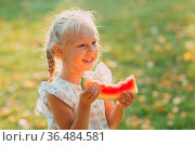 Cute blond little girl with watermelon on the grass in park. Стоковое фото, фотограф Zoonar.com/Max / easy Fotostock / Фотобанк Лори