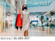 Young adult woman in protective medical face mask carrying paper shopping... Стоковое фото, фотограф Zoonar.com/Max / easy Fotostock / Фотобанк Лори