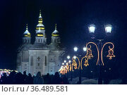 Beautiful city view with church and alley with new year lanterns.... Стоковое фото, фотограф Zoonar.com/Alexmak7 / easy Fotostock / Фотобанк Лори