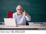 Old male teacher in front of green board. Стоковое фото, фотограф Elnur / Фотобанк Лори