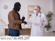 Masked man burglar bribing old doctor for getting vaccine. Стоковое фото, фотограф Elnur / Фотобанк Лори