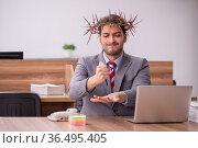 Young male employee wearing prickly wreath on head. Стоковое фото, фотограф Elnur / Фотобанк Лори