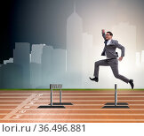Businessman jumping over barriers in business concept. Стоковое фото, фотограф Elnur / Фотобанк Лори