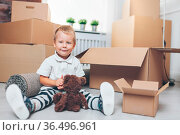 Cute toddler helping out packing boxes and moving. Стоковое фото, фотограф Zoonar.com/Tomas Anderson / easy Fotostock / Фотобанк Лори