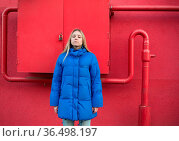 Girl in blue jacket stands on the background of a pink wall with pipes. Стоковое фото, фотограф Zoonar.com/OLGAMURiNA / easy Fotostock / Фотобанк Лори
