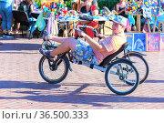 Russia, Samara, June 2021: A young man rides a recumbent bike along the Volga river embankment at the Volgafest festival on a sunny summer day. Редакционное фото, фотограф Акиньшин Владимир / Фотобанк Лори