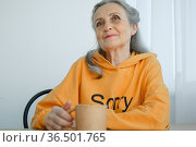 Happy elderly pensioner, eccentric gray-haired woman in yellow is drinking tea, looking thoughtfully into a mug. Стоковое фото, фотограф Ольга Балынская / Фотобанк Лори