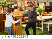 Man and woman choose wardrobe and chest of drawers in furniture store. Стоковое фото, фотограф Яков Филимонов / Фотобанк Лори