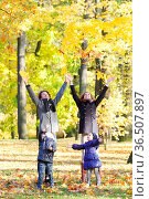 Happy family playing with autumn maple leaves in park. Стоковое фото, фотограф Zoonar.com/Tatiana Badaeva / easy Fotostock / Фотобанк Лори