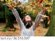 Happy Woman Throwing Leaves in autumn park. Стоковое фото, фотограф Zoonar.com/DAVID HERRAEZ CALZADA / easy Fotostock / Фотобанк Лори