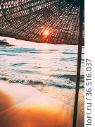 Umbrella On Sandy Beach. Sun Sunshine Through Wicker Umbrella At Summer... Стоковое фото, фотограф Ryhor Bruyeu / easy Fotostock / Фотобанк Лори