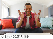 Happy caucasian man sitting on couch having video call in living room, smiling and gesturing. Стоковое фото, агентство Wavebreak Media / Фотобанк Лори