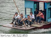 Locals travel along the Li River in a motorboat (2010 год). Редакционное фото, фотограф Александр Карпенко / Фотобанк Лори