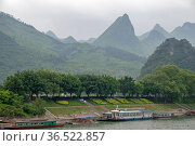 View of the Li River against the backdrop of beautiful mountains on a cloudy day (2010 год). Редакционное фото, фотограф Александр Карпенко / Фотобанк Лори