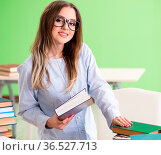 The young female student preparing for exams with many books. Стоковое фото, фотограф Zoonar.com/Elnur Amikishiyev / easy Fotostock / Фотобанк Лори