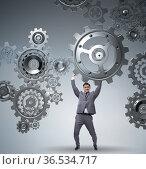 Businessman supporting gear in teamwork concept. Стоковое фото, фотограф Elnur / Фотобанк Лори