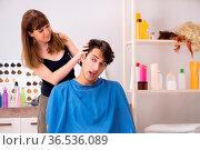 Young attracrive man visiting female barber. Стоковое фото, фотограф Zoonar.com/Elnur Amikishiyev / easy Fotostock / Фотобанк Лори