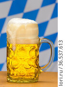Münchner Bier im bayerischen Maßkrug vor Bayern-Fahne in weiß-blau. Стоковое фото, фотограф Zoonar.com/Wolfilser / easy Fotostock / Фотобанк Лори