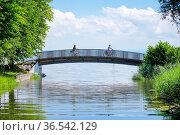 Zwei Fahrradfahrer überqueren die Brücke über den Bach Aach bei der... Стоковое фото, фотограф Patrick Frischknecht / age Fotostock / Фотобанк Лори