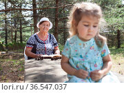 The girl was offended by her grandmother, granny wants to read a book for granddaughter, summer forest. Стоковое фото, фотограф Кекяляйнен Андрей / Фотобанк Лори