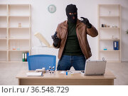 Young man in balaclava stealing vaccine from the lab. Стоковое фото, фотограф Elnur / Фотобанк Лори