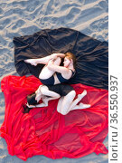 Two lovely girls in black bathing suits lie on red and black fabric on sandy beach. View from above. Стоковое фото, фотограф Евгений Ткачёв / Фотобанк Лори