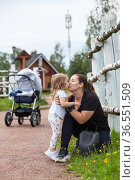 Mother kissing and embracing her little daughter in the park. People walking with baby stroller. Стоковое фото, фотограф Кекяляйнен Андрей / Фотобанк Лори