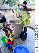Mother with baby on back collecting water from well, girl looking at camera in foreground, Formosa Island, Bijagos UNESCO Biosphere Reserve, Guinea Bissau, February 2015. Стоковое фото, фотограф Enrique Lopez-Tapia / Nature Picture Library / Фотобанк Лори