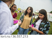 A happy, diverse group of girl friends share tickets at the county... Стоковое фото, фотограф Lori Epstein / age Fotostock / Фотобанк Лори