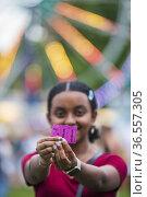 An African girl shows off her ride ticekts at a county fair. Редакционное фото, фотограф Lori Epstein / age Fotostock / Фотобанк Лори