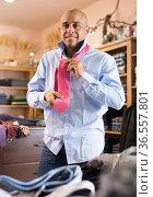 Man choosing new tie in clothing boutique. Стоковое фото, фотограф Яков Филимонов / Фотобанк Лори