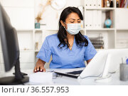 Female physician in protective mask filling up medical forms on laptop. Стоковое фото, фотограф Яков Филимонов / Фотобанк Лори