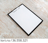 Photo of clipboard with a blank sheet of paper on light wooden background... Стоковое фото, фотограф Zoonar.com/Alex Veresovich / easy Fotostock / Фотобанк Лори
