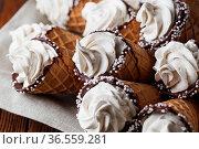 A lot of ice cream cones on wooden table. Soft ice creams or frozen... Стоковое фото, фотограф Zoonar.com/NATALIIA ZHEKOVA / easy Fotostock / Фотобанк Лори