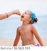 A child eats a grape on the beach. Mom#39,s hand feeding baby. Baby... Стоковое фото, фотограф Zoonar.com/Alex Veresovich / easy Fotostock / Фотобанк Лори