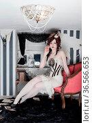 Junge Frau im Designer Vintage Kostüm in einem sehr kleinen Zimmer... Стоковое фото, фотограф Zoonar.com/Lars Patzek / easy Fotostock / Фотобанк Лори